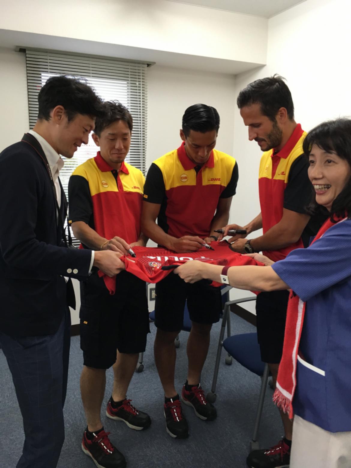 浦和レッズのユニフォームにその場でサインをする3選手