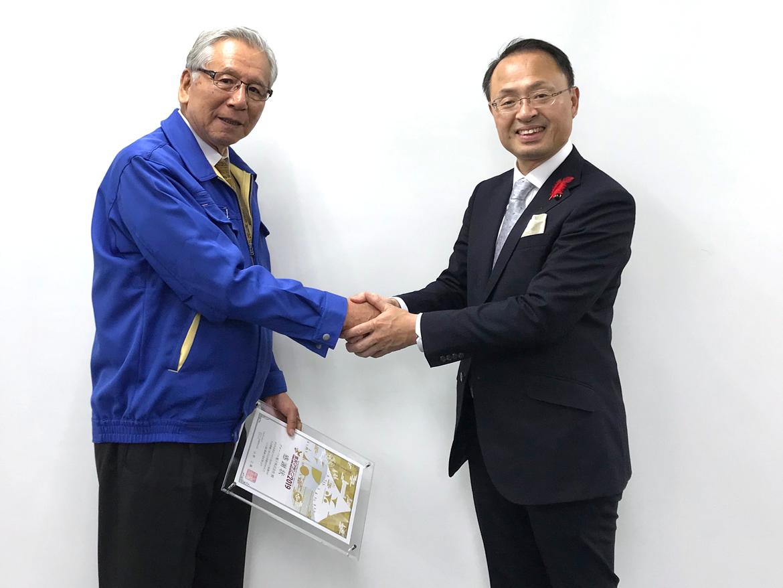握手を交わす山野金沢市長(右)と弊社松田会長(左)